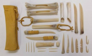 A replica bone toolkit depicting : hide fleshing tools, chisels, harpoon heads, awls, fishhooks, needles, needle case, knife. photo credit :http://www.dayofarchaeology.com/tag/native-american/