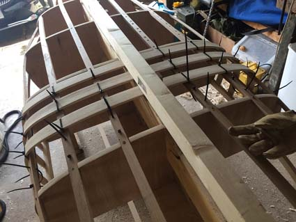Installing Ash ribs over canoe mold after steaming.