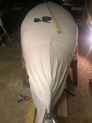 10oz canvas being fitted to the hull of the canoe.